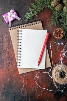 Akcesoria do dekoracji gałęzi jodłowych i prezentów i zeszytów z piórem na ciemnym tle