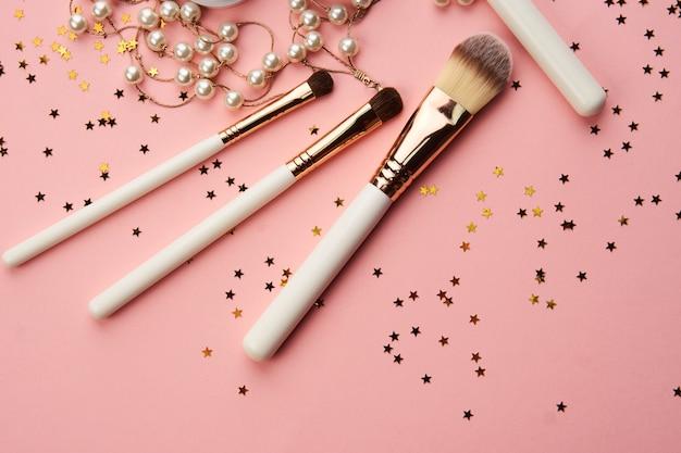 Akcesoria do dekoracji kobiecego makijażu na stole różowe tło widok z góry. wysokiej jakości zdjęcie