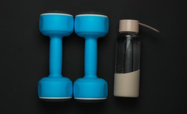 Akcesoria do fitnessu i sportu na czarnym tle. hantle, butelka wody. widok z góry, płaski układ