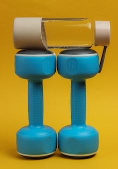Akcesoria do fitnessu i sportu na żółtym tle. hantle, butelka wody.