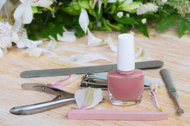 Akcesoria do manicure: lakier do paznokci nude, pilnik diamentowy, zmywacz do skórek, maszynka do strzyżenia i popychacz do paznokci. koncepcja manicure w domu.
