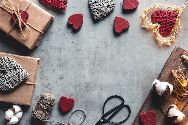 Akcesoria do pakowania prezentów. prezenty w papier rzemieślniczy na szarym tle. walentynki, niespodzianka i bawełniane kwiaty
