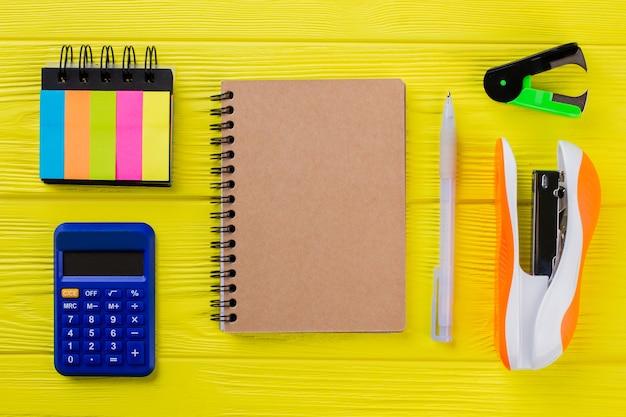 Akcesoria do papeterii płaskie świeckich na żółtym stole. notatnik z kalkulatorem i zszywaczami.