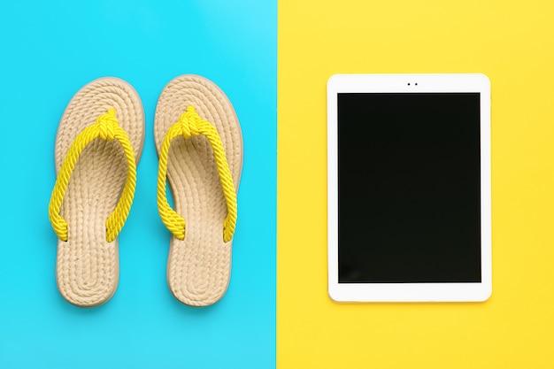 Akcesoria do pływania - modne letnie klapki, tablet z czarnym ekranem