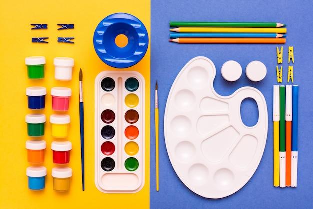 Akcesoria do rysowania ołówków, pisaków, akwareli, gwaszów i pędzli na żółtym kolorze