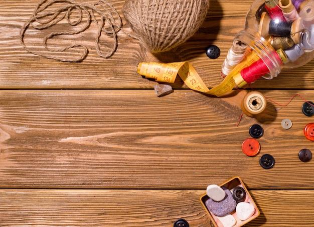 Akcesoria do szycia, takie jak nici i igły, na drewnianym stole. skopiuj miejsce. koncepcja pracy domowej