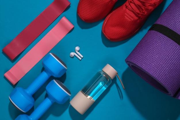 Akcesoria do uprawiania sportu lub fitnessu na jasnoniebieskim tle.
