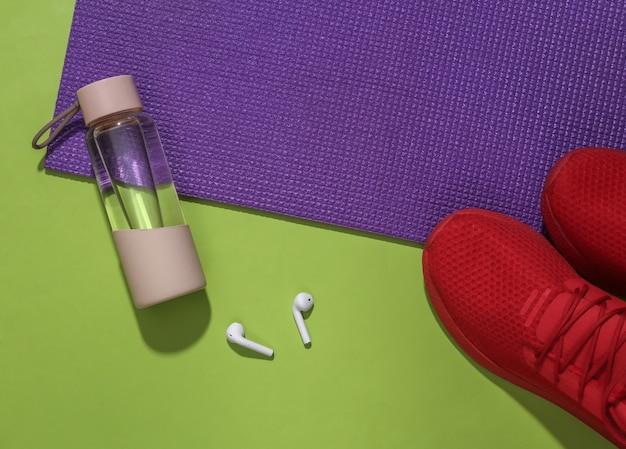 Akcesoria do uprawiania sportu lub fitnessu na jasnozielonym tle.