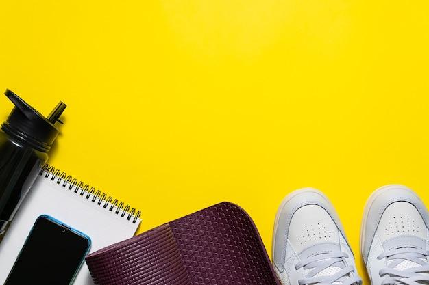 Akcesoria fitness na jasnożółtym tle.