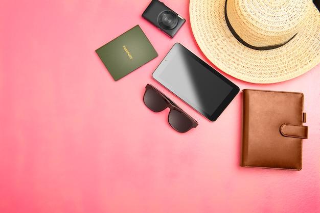 Akcesoria i wyposażenie, takie jak kapelusz, portfel, aparat fotograficzny, tablet, okulary przeciwsłoneczne i paszport do podróży