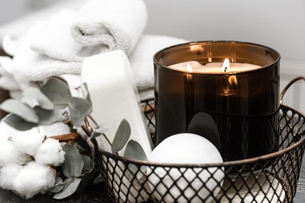 Akcesoria kąpielowe i płonąca świeca w koszu. koncepcja aromaterapii.