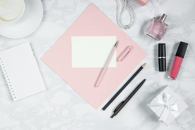 Akcesoria kobiece na białym marmurowym stole. różowa kartka papieru, długopis, notatnik, perfumy, pudełko, perły, szklanka kawy