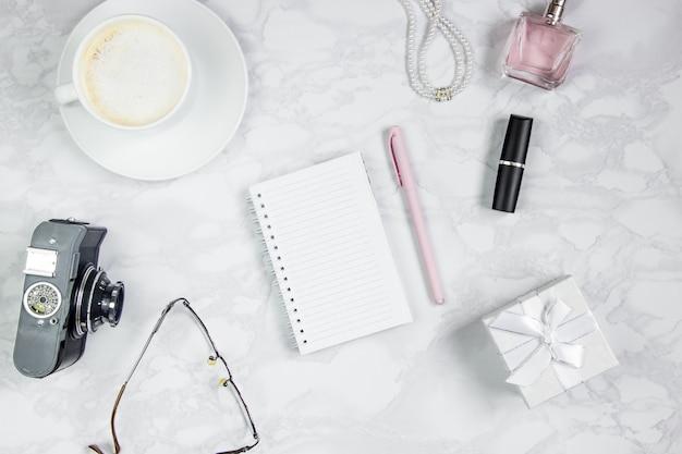 Akcesoria kobiece na białym marmurowym stole. różowa kartka papieru, długopis, notatnik, perfumy, pudełko, perły, szklanki, szklanka kawy