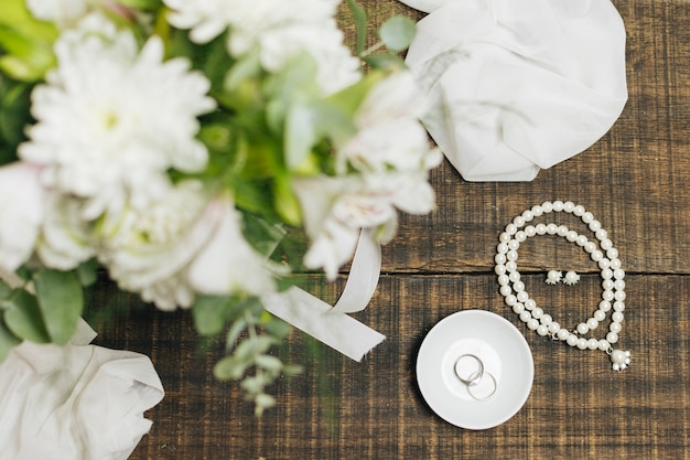 Akcesoria kobiece; obrączki ślubne ; szalik i bukiet kwiatów na stole