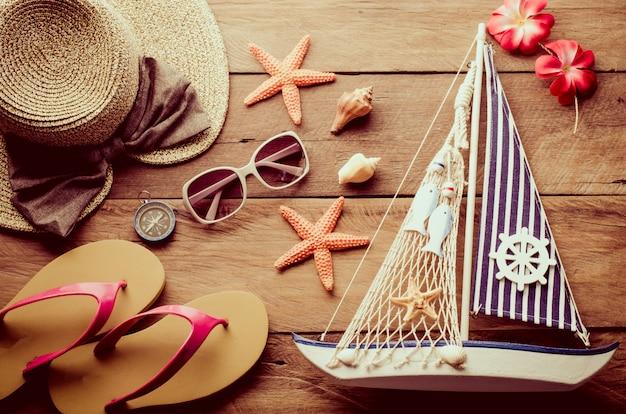 Akcesoria kostiumowe z podróżą na lato na drewnianej podłodze