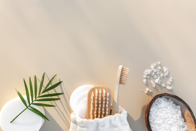 Akcesoria łazienkowe leżą płasko. naturalne składniki do pielęgnacji ciała. pojęcie opieki zdrowotnej, drewniana szczoteczka do zębów, szczoteczka do stóp, waciki, mydło. ekologiczne, zero odpadów, wielokrotnego użytku, wolne od plastiku środowisko