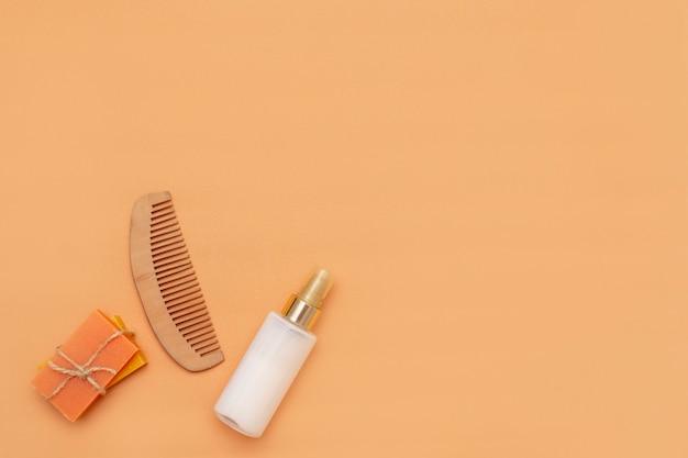 Akcesoria łazienkowe z bezodpadowymi kostkami mydła w płynie, sprayem kosmetycznym, drewnianym grzebieniem na beżowym tle