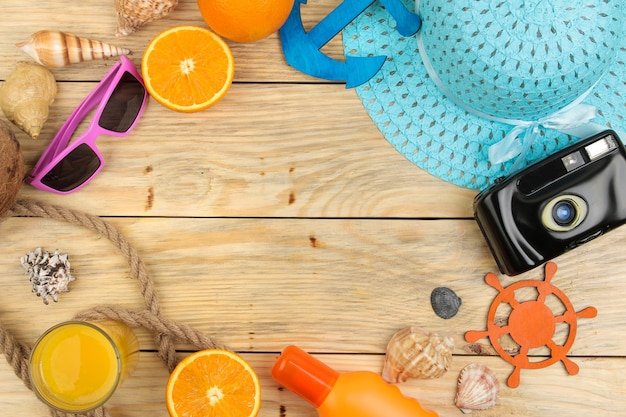 Akcesoria letnie. akcesoria plażowe. kapelusz, krem do opalania, okulary przeciwsłoneczne, aparat i pomarańcza na naturalnym drewnianym stole. widok z góry.