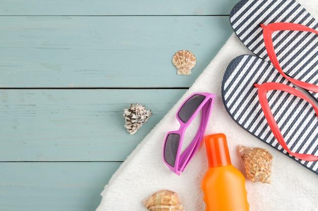 Akcesoria letnie. akcesoria plażowe. klapsy, ręcznik i okulary przeciwsłoneczne na niebieskim drewnianym stole. widok z góry.