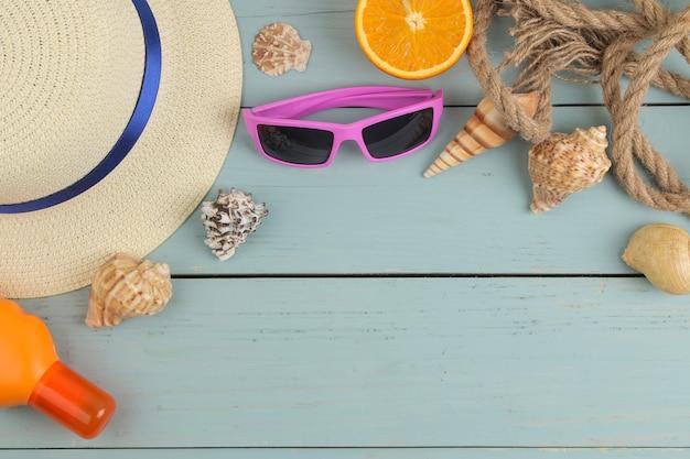 Akcesoria letnie. akcesoria plażowe. kremy przeciwsłoneczne, kapelusz, muszle i okulary przeciwsłoneczne na niebieskim drewnianym stole. widok z góry.