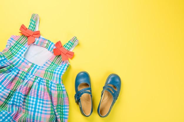 Akcesoria małej dziewczynki. kolorowa sukienka i buty na żółtej powierzchni.