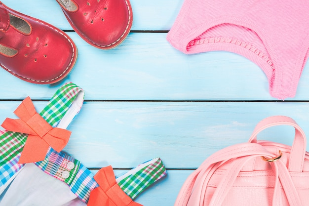 Akcesoria małej dziewczynki. różowa torba z kolorową sukienką, butami i koszulą na niebieskiej pastelowej powierzchni drewnianej.