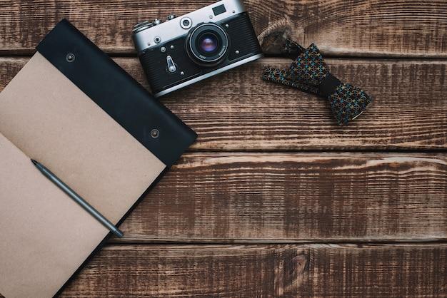 Akcesoria męskie muszka, aparat retro, notatnik na drewnianym stole. leżał płasko.