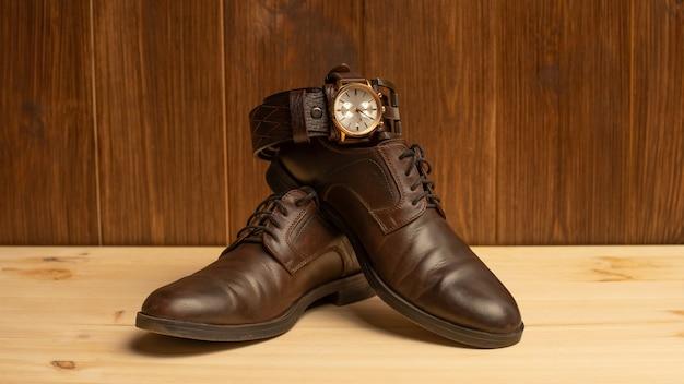 Akcesoria męskie z brązowym skórzanym paskiem, buty i zegarek na drewnianym tle