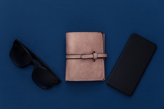 Akcesoria modowe damskie i smartfon na klasycznym niebieskim tle. kolor 2020. widok z góry.