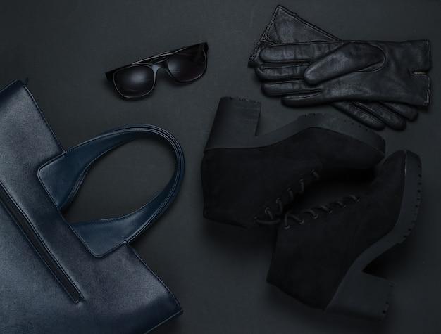 Akcesoria mody damskiej na czarnym tle. zamszowe buty, skórzana torba, rękawiczki, okulary przeciwsłoneczne. widok z góry