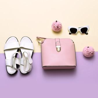 Akcesoria mody damskiej. różowa torba i okulary przeciwsłoneczne. modne sandały pastelowe kolory trend