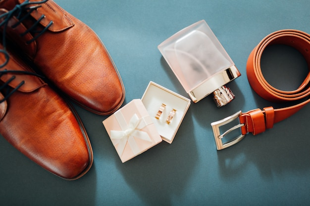 Akcesoria na dzień pana młodego. brązowe skórzane buty, pasek, perfumy, złote pierścienie