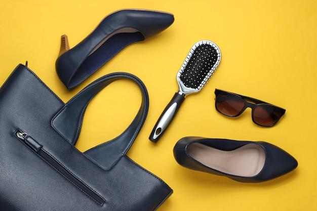 Akcesoria odzieżowe damskie płaskie świeckie na żółtym tle torba skórzane buty na wysokim obcasie okulary przeciwsłoneczne grzebień