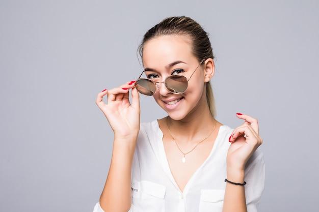 Akcesoria, okulary, moda, ludzie i luksus - piękna młoda kobieta w eleganckich czarnych okularach przeciwsłonecznych na szarej ścianie