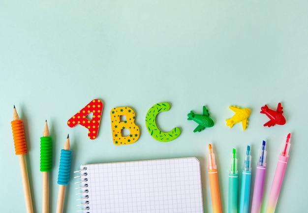 Akcesoria papiernicze i pusty notatnik na niebieskim tle. skopiuj miejsce na tekst, powrót do koncepcji szkoły.