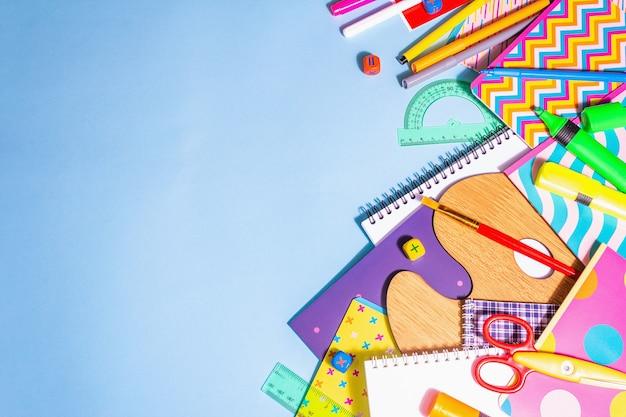 Akcesoria papiernicze na niebieskim tle. artykuły szkolne, ołówki, farby, nożyczki i kolorowe zeszyty. koncepcja edukacji i pracy niezależnej, widok z góry