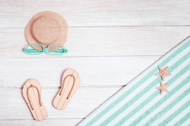 Akcesoria plażowe. buty letnie - klapki, bawełniany ręcznik, czapka od słońca, okulary przeciwsłoneczne