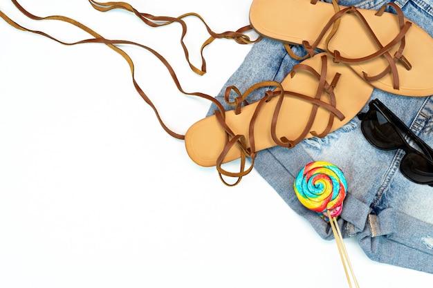 Akcesoria plażowe leżące na płasko. widok z góry koncepcja podróży lub wakacji. kopiowanie miejsca jean, sandały, okulary przeciwsłoneczne i lollypop