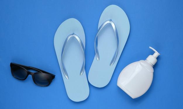 Akcesoria plażowe. modne klapki plażowe, butelka z kremem z filtrem, okulary przeciwsłoneczne na niebieskim papierze
