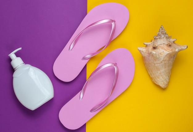 Akcesoria plażowe. modne plażowe różowe klapki, butelka z kremem z filtrem, muszla na fioletowym żółtym tle papieru.