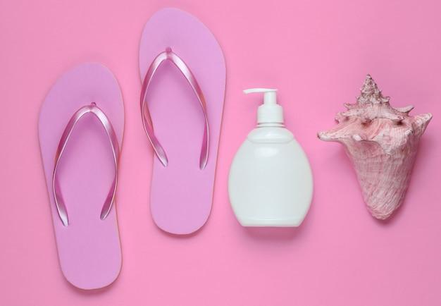 Akcesoria plażowe. modne plażowe różowe klapki, butelka z kremem z filtrem, muszla na różowym papierze