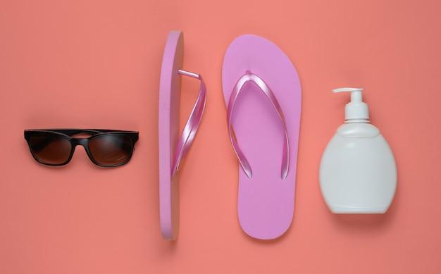 Akcesoria plażowe. modne plażowe różowe klapki, butelka z kremem z filtrem, okulary przeciwsłoneczne na różowym papierze