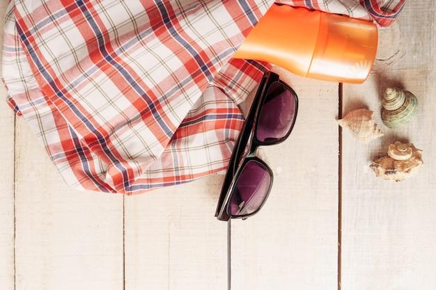 Akcesoria plażowe na białym drewnianym stole płasko leżał skład widok z góry. krem do opalania, okulary przeciwsłoneczne, letni kapelusz, muszle.