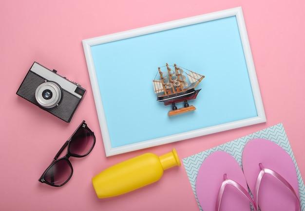 Akcesoria plażowe na różowej, pastelowej powierzchni z ramką na zdjęcie