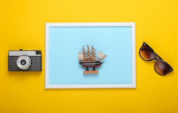 Akcesoria plażowe na żółtej powierzchni z ramką