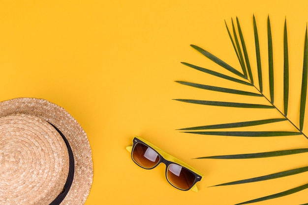 Akcesoria plażowe: okulary i czapka z muszlami i morskimi gwiazdami na kolorowym tle. lato w tle