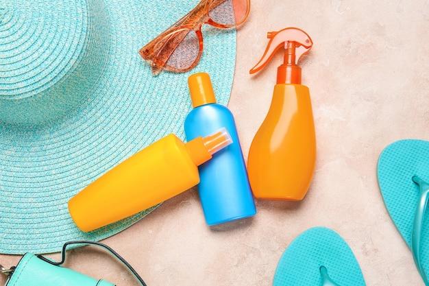 Akcesoria plażowe z kremem przeciwsłonecznym na kolorowym tle