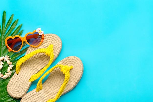 Akcesoria pływackie - krem do opalania, okulary w kształcie serca, żółte klapki, dłoń, bransoletka muszle na białym tle