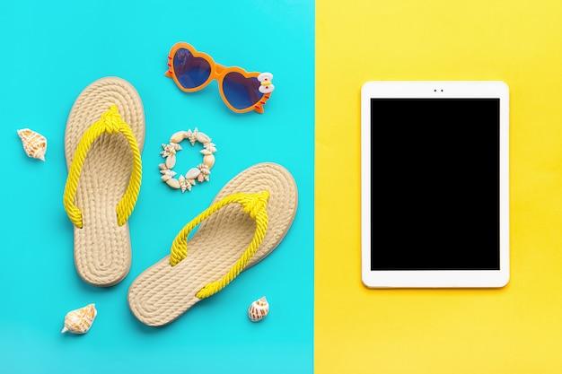 Akcesoria pływackie - modne okulary w kształcie serca, letnie klapki, muszle, tablet