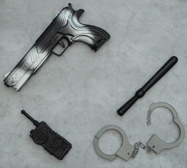 Akcesoria policjanta, detektywa lub agenta specjalnego, kajdanki, radiostacja, pistolet, pałka